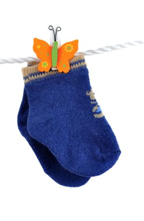 Cute blue baby socks hanging on a cord, isolated on white photo