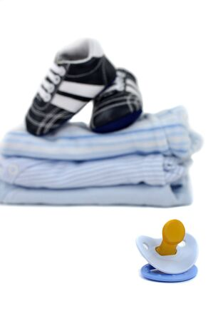Blue pacifier and shoes on a pile of clothes, isolated on white Stock Photo - 5142570