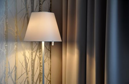 lit lamp: Lit lamp by the curtains in the modern room