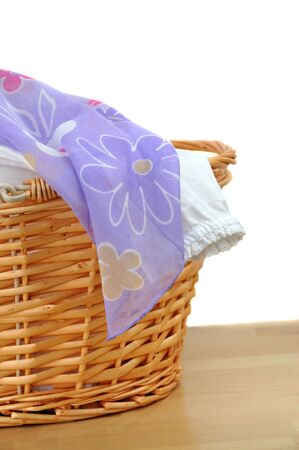 Lovely white and purple laundry in a wicker basket, isolated on white photo