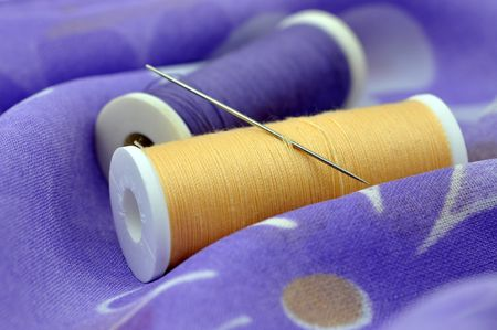 Needle and spools on floral cloth photo