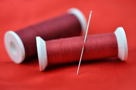 Needle and spools on red cloth Stock Photo - 6564638