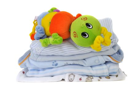 Colorful toy on a pile of soft blue baby clothes