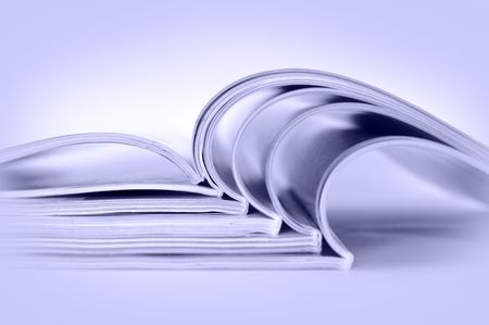 Stack of open magazines, toned blue Stock Photo