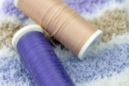 Two spools on soft striped textile Stock Photo - 6614056