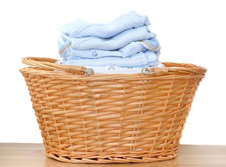 Folded blue baby laundry in a wicker basket Standard-Bild