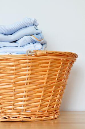 Folded blue baby laundry in a wicker basket Stock Photo