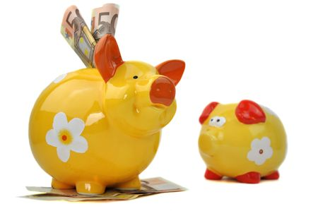Small empty piggy bank sadly looking at big happy piggy bank full of money Stock Photo - 6791266