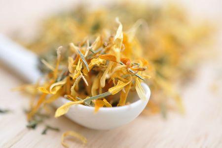 Pot marigold herbal tea in a ceramic spoon