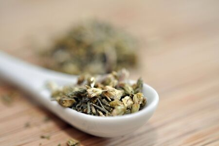 Yarrow herbal tea with in white spoon photo
