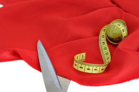 Measuring tape and scissors on red textile photo