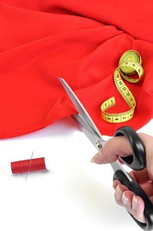 Seamstress cutting red textile Standard-Bild