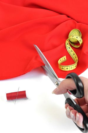 the textile industry: Seamstress cutting red textile Stock Photo