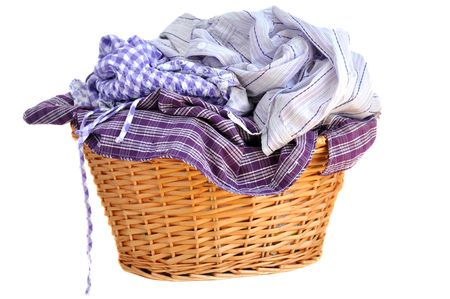 green clothes: Laundry in a wicker basket, isolated on white