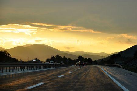 Autos fahren auf der Autobahn bei Sonnenuntergang