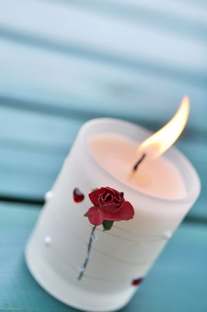 Burning white candle decorated with a rose and heart