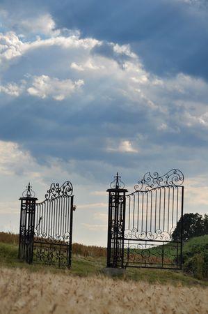 Open iron gates under the dramatic sky