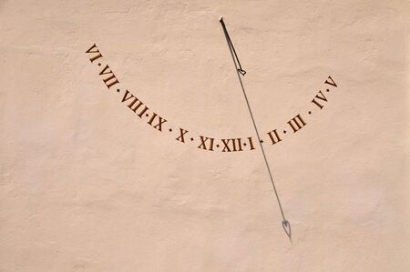 An old-fashioned sun dial on a wall photo