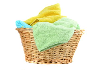 Towels in a wicker basket, isolated on white