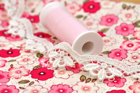 Spool and lace and on floral cloth Stock Photo - 8251578