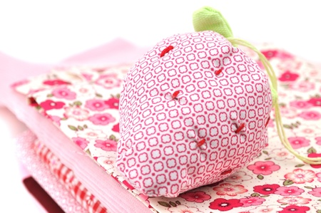 Strawberry pincushion on a pile of folded textile  Stock Photo - 8392043