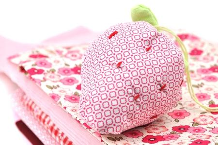 Strawberry pincushion on a pile of folded textile Stock Photo - 8392043