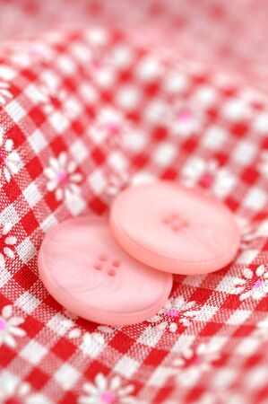 Pink buttons on checked textile photo
