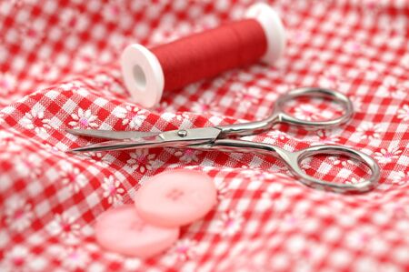 Pink buttons, scissors and thread on checked textile photo