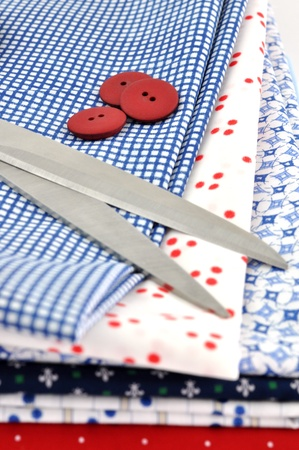 Scissors and buttons on a pile of folded textile Stock Photo - 8539149