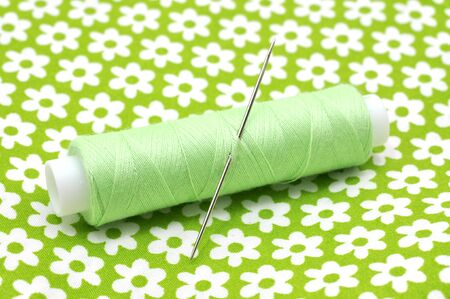 Green thread and needle on floral fabric Stock Photo - 8557497