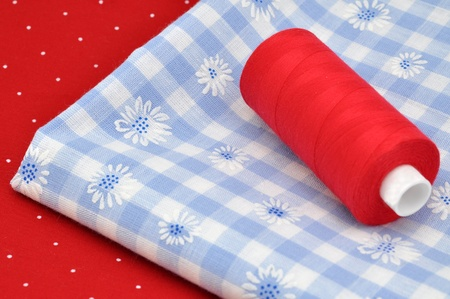 Red thread on blue and red fabrics Stock Photo - 8557500