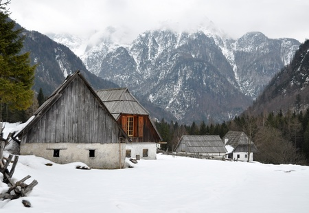 julian: Old alpine cottages in the Trenta valley with mountains in the background