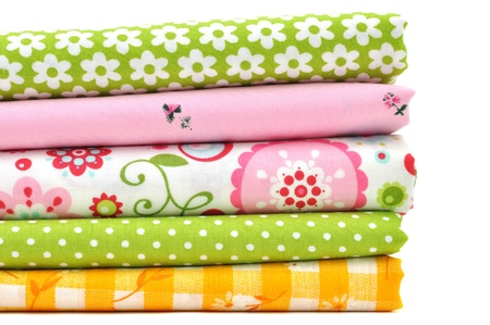 sewing item: Pile of colorful folded fabrics, isolated on white