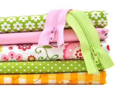 Zippers on a pile of folded fabrics Stock Photo