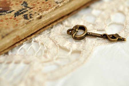 Vintage key on lace by the old book Stock Photo - 9383429