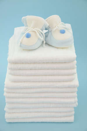 Blue baby slippers on a pile of cotton diapers  Stock Photo - 9977289