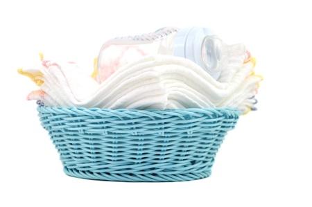 Baby bottle and diapers in a blue wicker basket photo