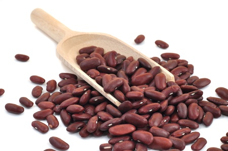 Red beans in a wooden scoop, isolated on white  photo