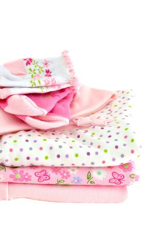 Pile of pink baby clothes, isolated on white photo