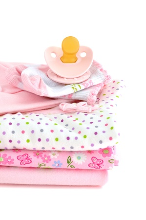 Pacifier and a pile of pink baby clothes, isolated on white photo
