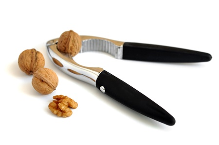 cracking: Freshly cracked walnut and nutcracker on white background Stock Photo