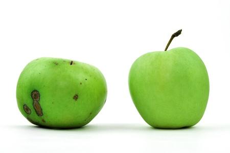 Een slechte en een perfecte groene appel, geïsoleerd op wit