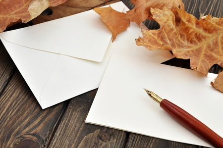 Fountain pen on empty letter with autumn leaves on a wooden table