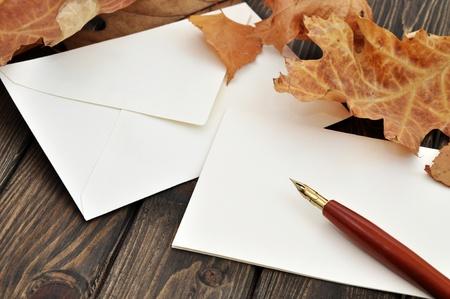 Füllfederhalter auf leere Buchstaben mit Herbstlaub auf einem Holztisch