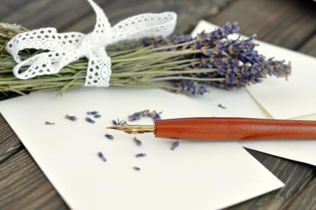 Füllfederhalter auf leere Buchstaben mit einem Blumenstrauß getrocknete Lavendel auf einem Holztisch
