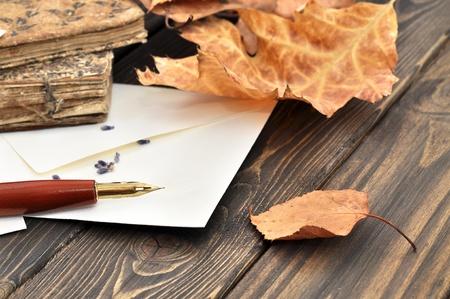 Füllfederhalter auf leere Buchstabe mit Herbstlaub und alten Büchern auf einem Holztisch