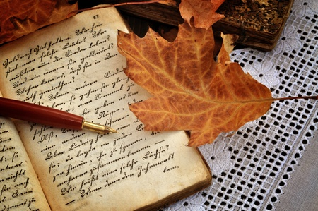 Fountain pen on old handwritten book with autumn leaves on a lacy tablecloth Standard-Bild