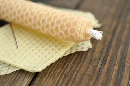 Beeswax handmade rolled candle and needle on honeycomb