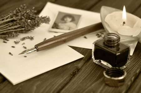 Fountain pen and old picture on empty letter with a bouquet of dried lavender and lit candle on a wooden table photo