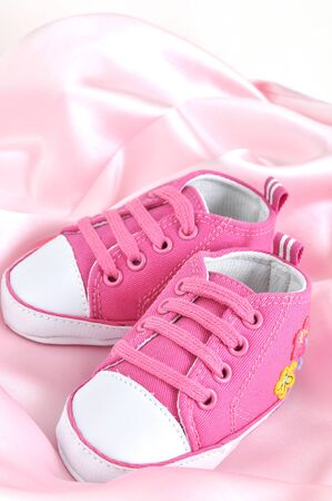 baby shoes: Pink baby booties on pink silk Stock Photo